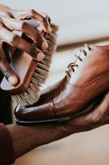 Man die schoensmeer aanbrengt op zijn bruine leren schoenen