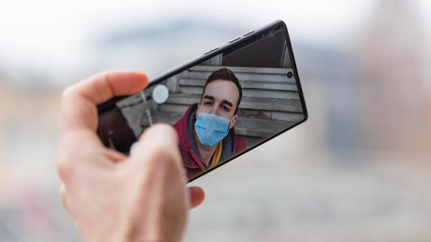 Man die selfie met smartphone neemt terwijl hij medische masker draagt