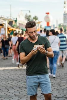 Man die straatvoedsel eet. hotdogs op straat