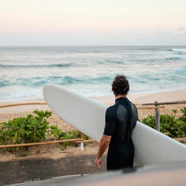 Man die surfer kleding draagt en zijn surfplank vasthoudt