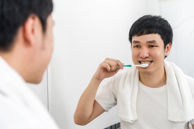 Man die tandenborstel gebruikt om tanden te poetsen in de badkamerspiegel