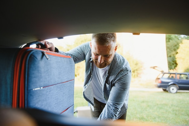 Man die tassen in de kofferbak stopt. klaar voor autoreizen. zonnige ochtend