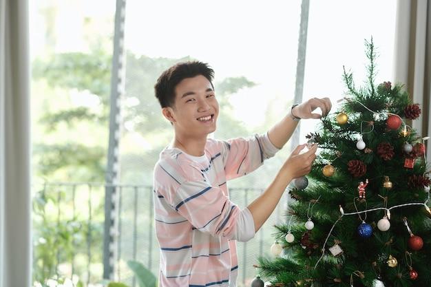 Man die thuis kerstversiering ophangt met een kerstbal in zijn hand
