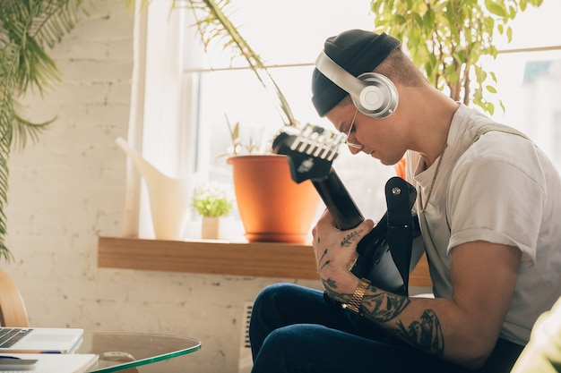 Man die thuis studeert tijdens online muziekcursussen.