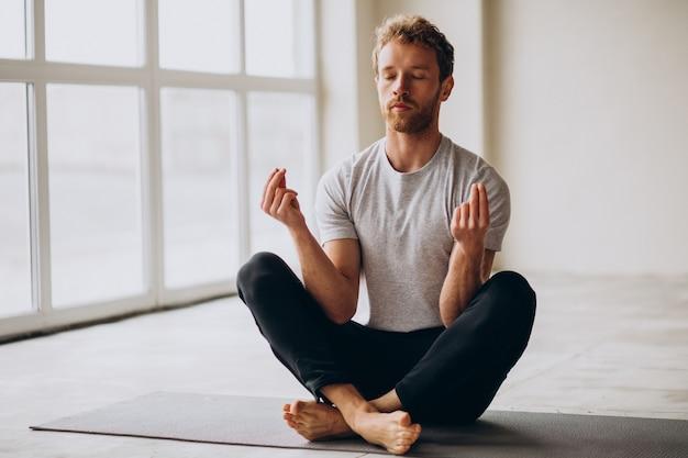 Man die thuis yoga beoefent op de mat