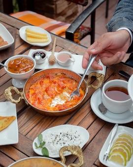Man die tomaat en ei schotel met vork bij traditioneel ontbijt