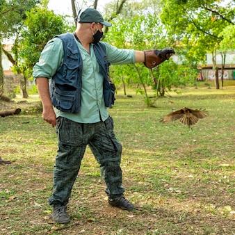 Man die valkerij traint met een havik parabuteo unicinctus
