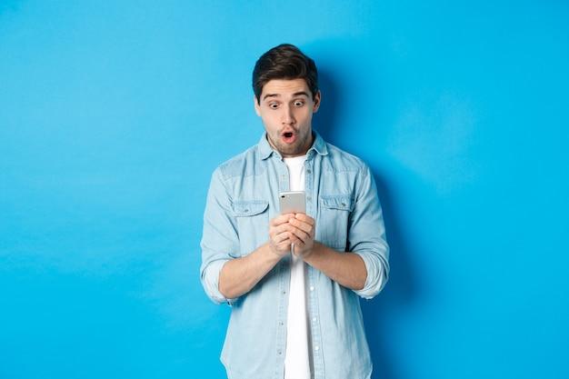 Man die verbaasd kijkt terwijl hij promo op smartphone controleert, verbaasd naar de telefoon kijkt en tegen een blauwe achtergrond staat
