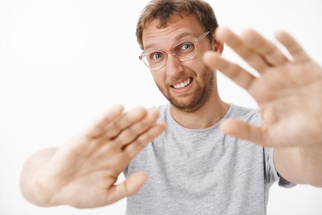 Man die verlegen voelt, haat het om gefotografeerd te worden terwijl hij zijn handen naar het gezicht trekt om het gezicht te bedekken met zaklantaarn, waardoor een verward, onhandig gezicht wenkbrauwen optrekt en met zijn ogen dichtknijpen zich ongemakkelijk voelt