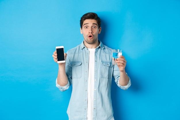 Man die verrast kijkt, smartphonescherm en glas water toont, staande over blauwe achtergrond