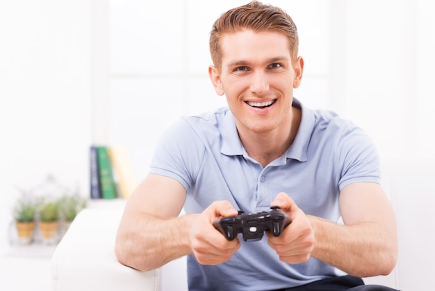 Man die videogame speelt. gelukkige jonge man die joystick gebruikt terwijl hij thuis een videogame speelt