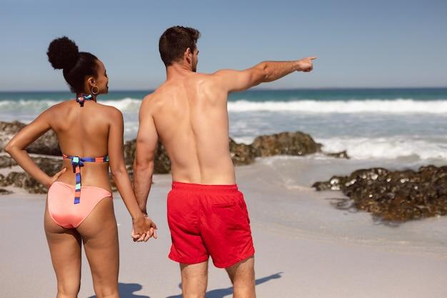 Man die vinger richt en iets toont aan vrouw bij strand in de zonneschijn