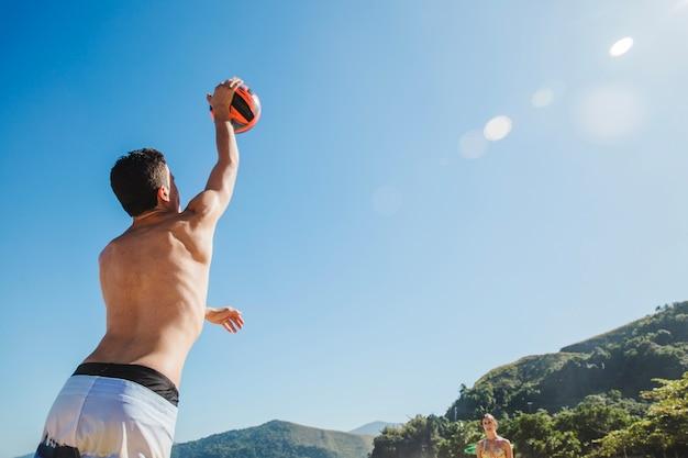 Man die volleyball op een zonnige dag serveert