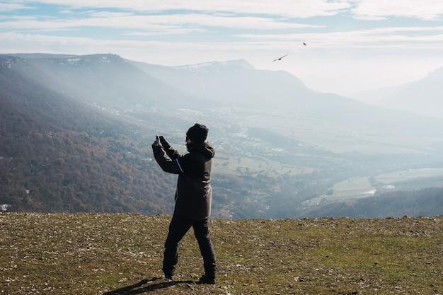 Man die voor een klif staat en met een mobiel foto's maakt van met mist bedekte bergen.