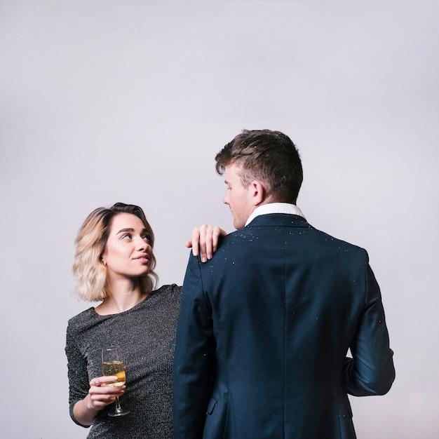 Man die vrouw met champagneglas bekijkt