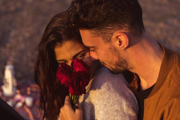 Man die vrouw met rode rozen koestert