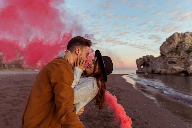 Man die vrouw met rookbom koestert op overzeese kust