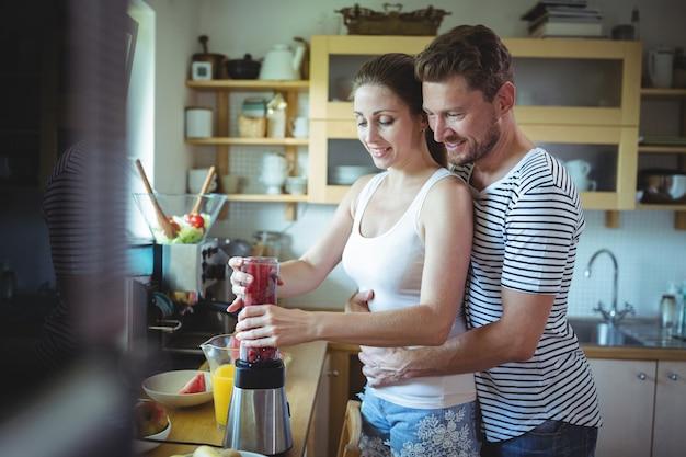 Man die vrouw van erachter omhelst terwijl het voorbereiden van watermeloen smoothie in de keuken