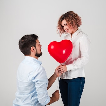 Man die vrouwenballon geeft voor valentijnskaarten
