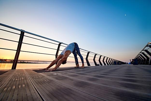 Man die yoga beoefent bij zonsondergang en hond met zijn gezicht naar beneden doet