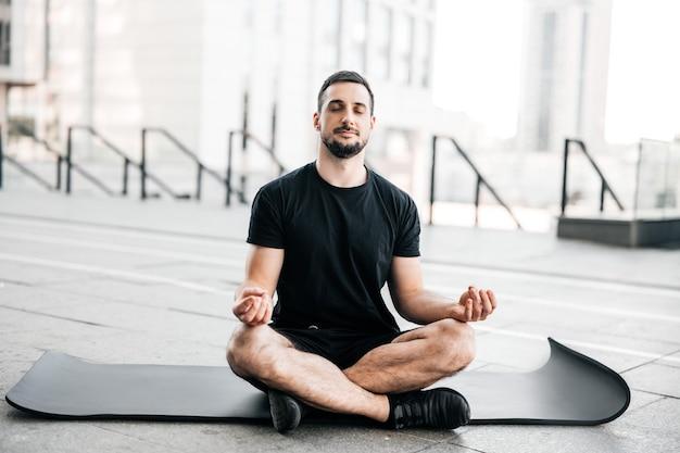 Man die yoga beoefent in de grote stad. sportieve man mediteren na training. thuis sporten. jonge man met stoppels zittend op zwarte yogamat met gesloten ogen buitenshuis en ontspannen in gemakkelijke stoel pose.