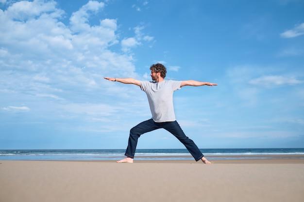 Man die yoga beoefent op een strand op een zonnige dag