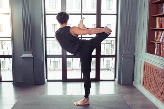 Man die yoga beoefent tegen een stedelijke achtergrond met groot raam