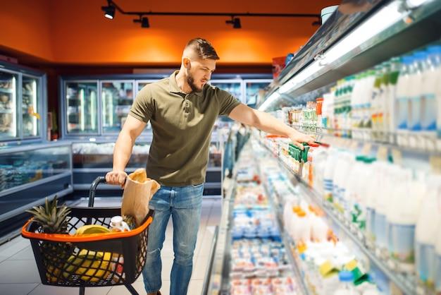 Man die yoghurt kiest in de supermarkt, afdeling zuivelproducten