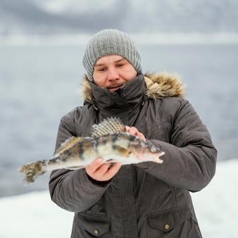Man die zegevierend een vis vasthoudt die hij heeft gevangen