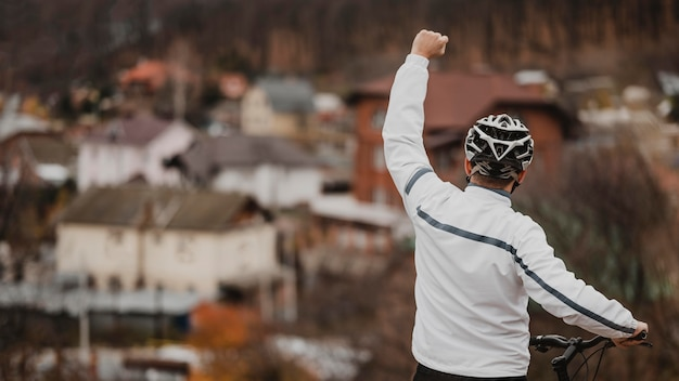 Man die zegeviert na het rijden op zijn fiets met kopie ruimte