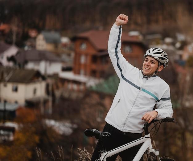Man die zegeviert na het rijden op zijn fiets