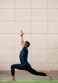 Man die zich uitstrekt buiten tijdens het doen van yoga