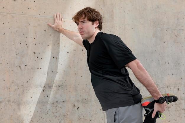 Man die zich uitstrekt buiten voordat u gaat trainen