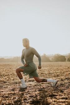Man die zich uitstrekt en traint in sportkleding bij zonsondergang op het platteland