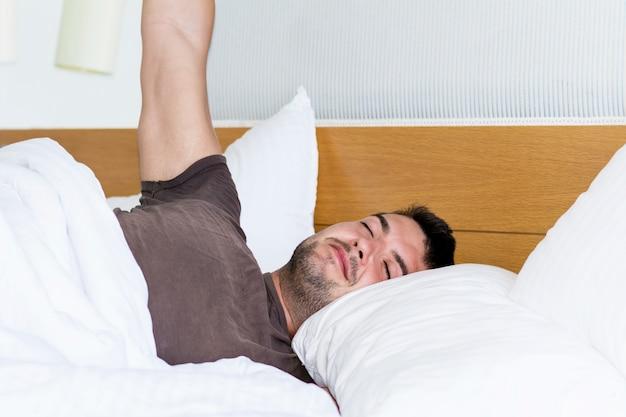 Man die zich uitstrekt in bed na het ontwaken