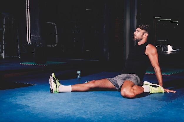 Man die zich uitstrekt in de sportschool