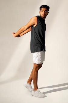 Man die zich uitstrekt in marineblauwe tanktop en korte sportkledingwear