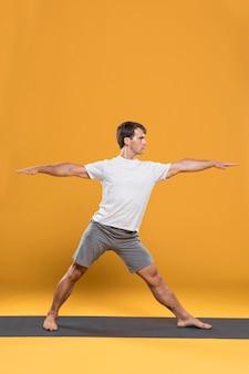 Man die zich uitstrekt over yoga mat