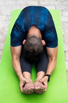 Man die zich uitstrekt tijdens het doen van yoga buiten