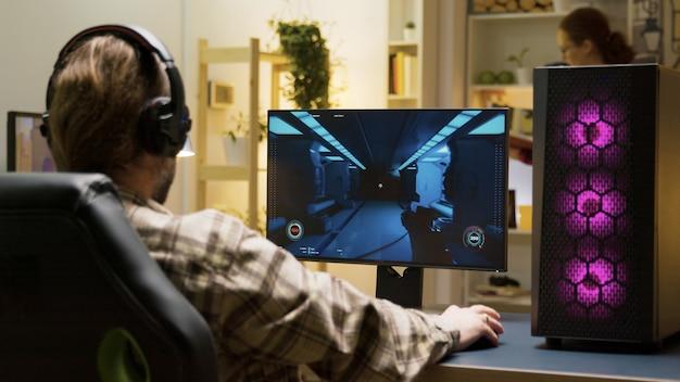 Man die zich uitstrekt voordat hij videogames begint te spelen op een computer die op een gamingstoel zit.