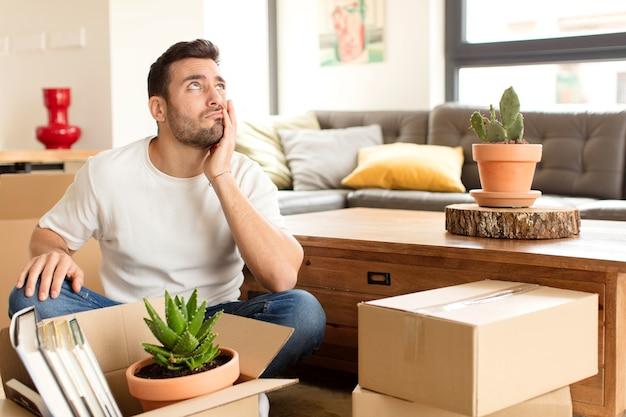 Man die zich verveeld, gefrustreerd en slaperig voelt na een vermoeiende, saaie en vervelende taak, het gezicht met de hand vasthoudend