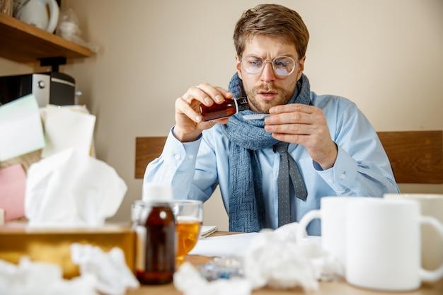 Man die zich ziek en moe voelt. man met beker thuis werken, zakenman verkouden, seizoensgriep.