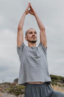 Man die zijn armen opheft terwijl hij buiten yoga doet
