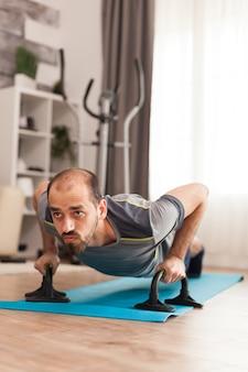 Man die zijn borstspieren traint en push-ups doet in de tijd van een uitbraak van het coronavirus.