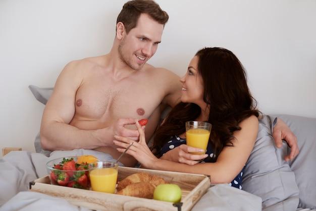 Man die zijn geliefde voedt met aardbeifruit