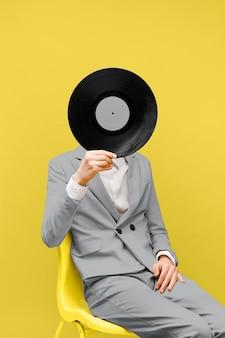Man die zijn gezicht bedekt met een vinylplaat terwijl hij ultieme grijze kleding draagt