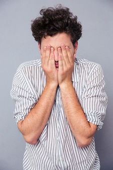 Man die zijn gezicht bedekt met handpalmen