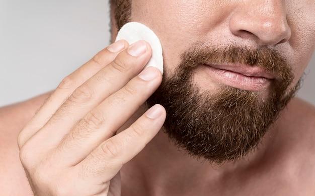 Man die zijn gezicht met een reinigingsschijf schoonmaakt