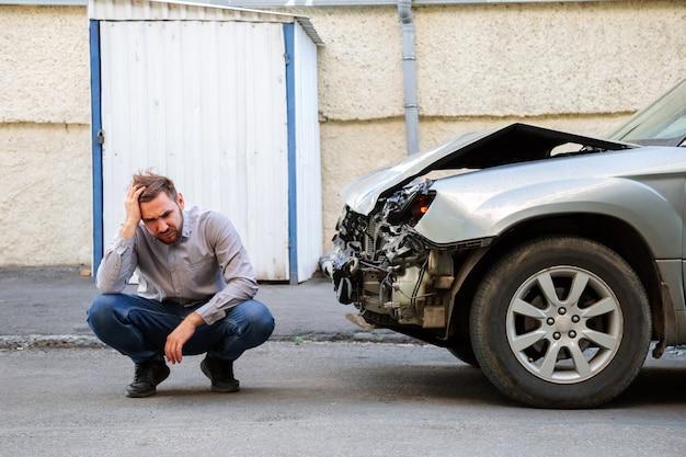 Man die zijn hoofd vasthoudt en gefrustreerd lijdt na een auto-ongeluk. bestuurder houdt hoofd in de buurt van de vernielde auto na auto-ongeluk op de weg.