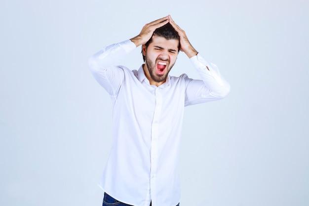 Man die zijn hoofd vasthoudt vanwege hoofdpijn of zich uitgeput voelt
